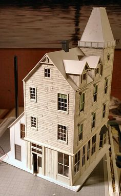 Make the tower roof with styrene sheets. A Grandt Line brick chimney was added to the roof. Make a simple kitchen wing/boiler house on the back from board and batten styrene sheet, a window and a door plus a large drinking straw.