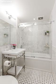 Upper East Side Bathroom features white marble floor tiles accented with black diamond tiles, radiant floor heating, and marble square tiles from Home Depot.