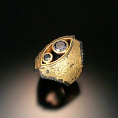 """Aurora UA"" ring. Textured iron fused with 20 karat gold. Aurora color-change garnet and black rose cut diamond set in 22 karat gold. This piece will be in the printed catalog for FERROUS Exhibiton at Velvet da Vinci March 1-April 14. The exhibition may move to Toronto for the SNAG Conference and from there maybe England. https://www.facebook.com/142559672451871/photos/a.499218103452691.102714.142559672451871/499218230119345/?type=3"
