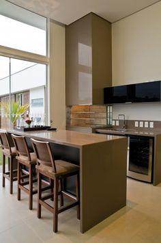A cozinha, totalmente integrada ao jantar, apresenta bancada com fogão em ilha, com acaba- mentos em madeira e vidro acidato espelhado bronze.