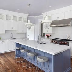We love the hints of color in this white kitchen design by Annette Jaffe Interiors The Classic Colonial kitchen has lavender ceilings and a coordinating sweet blue island. Photo by T Williams Photo.