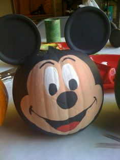 Mickey pumpkin... I spray painted the whole pumkin black,  then painted the face with acrylics. The ears are flat lids to mason jars sprayed black.  They are taped to a toothpick, and the toothpick is stuck into the pumpkin.