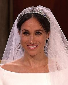 Meghan Markle looks elegant in slight off shoulder neckline custom Clare Waight Keller Wedding Gown with a dramatic train. Her hair was up and she wore the glittering Queen Mary's Diamond Bandeau tiara, loaned to her by the Queen