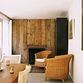 Wohnzimmer mit rustikaler Holzwand und Korbmöbel – living4media