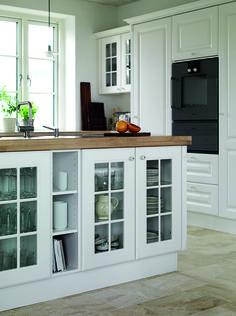 Stilen i landkøkkenet understreges af sprossede vitrineskabe, åbne hylder og de charmerende piedestaler.