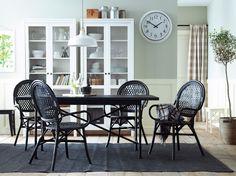 En spisestue med et sort spisebord og stole af rotting. Kombineret med 2 hvide vitrineskabe.