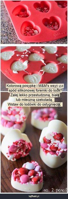 Słodki prezent na walentynki - Kolorową posypkę i M&M\'s wsyp na spód silikonowej foremki do lodu. Zalej lekko przestudzoną, białą lub mleczną czekoladą.  Wstaw do lodówki do ostygnięcia.