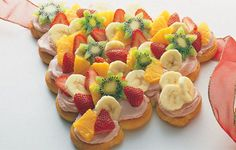 1 can Pillsbury Crescent rolls*  1 tub spreadable cream cheese w/ raspberries, pineapple or blueberries fruit flavor.2 Tb powdered sugar,   sliced strawberries, kiwi, mandarine oranges,grapes & banana.Shape as a tree & bake as directed .Remove from pan carefully & place on platter.Mix cream cheese & sugar, spread on tree when cooled . Decorate w/ fruit.
