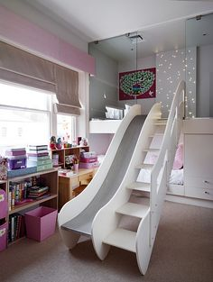a ladder and slide in the room that goes up into a little step up, play room. This is a bedroom or playroom for little kids if you take the pink away it could be for boys and girls room. This is some brilliant designing! Love it