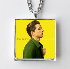 "This is a necklace featuring album art of the ""Nine Track Mind"" record by Charlie Puth sealed in a silvertone metal setting. The album cover pendant is 1"" and on a 20"" long silvertone neck chain. The"