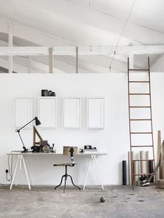 Minimal sawhorse desk/table with industrial stool in white vaulted ceiling studio space.