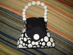 """Looking for a unique one-of-a-kind gift for someone who sews, quilts or does other needle work?   This is the perfect gift!  A purse pin cushion.  This pincushion in the shape of a purse is useful and attractive! Made from revalued capri's this pincushion is black with white dots, a black flap with decorative button and white bead handle on wired to hold it's shape.  The inside is stuffed with fine sand and poly-fill.      Approximate measurements: Base - 4.25"""" X 1.5"""" Heigh..."""