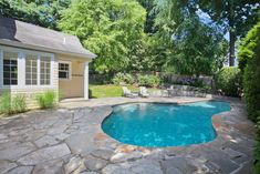 pool house. stone patio. seating area. pool. landscaping.