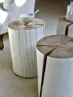 Painted wood stumps used as small tables retain their natural feeling. The tree's rings create a concentric pattern on the tops while cracks and bumps add texture to the sides.