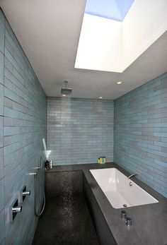 The master bathroom has a skylight that achieves a similar effect as the deck sun structure. Combined with ocean-hued Heath subway tiles and basalt tub surround, the master bath is a microcosm of sea, sky and earth.