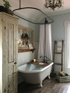 A shabby chic farmhouse bathroom with grey printed wallpaper, a white clawfoot tub, a shabby chic storage unit, a mirror in a wooden frame. Vintage Bathrooms, Vintage Bathroom Decor, Farmhouse Bathrooms, Country Bathrooms, Vintage Bathtub, Bohemian Bathroom, Chic Bathrooms, Bath Decor, Antique Bathtub