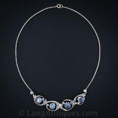 4 brillantes 'destello azul' piedras lunares flotan dentro de gracia coronas de diamantes estilizadas en este raro y deslumbrante collar antiguo de finales del siglo 19. Plata sobre el oro.