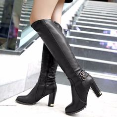End up your outfit with this pair of boots. A knee high boots with a side zipper closure, squared high heel, glossy and a buckle detail, a soft fur inside to make your foot nice and warm. This design