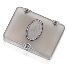 PLATINUM, AGATE, SAPPHIRE AND DIAMOND BOX, CARTIER, PARIS The agate box centering an oval-shaped reverse intaglio crystal depicting a dancin...