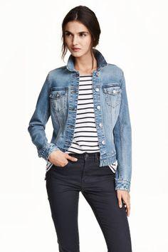 1.000,- Džínová bunda: Mírně projmutá džínová bunda ze sepraného denimu. Má obnošené detaily, patkové náprsní kapsy s knoflíkem a nastavitelné pásky a knoflíky po stranách.