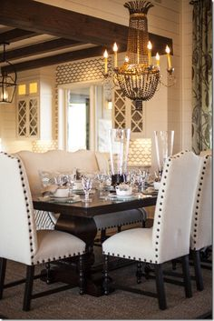 Dark rustic table.  Lightly colored parson's chairs with nail heads.  Dramatic chandelier.