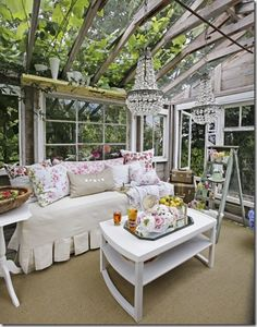 Old windows, chandeliers and upholstered furniture beneath a pergola, create the illusion of an indoor room in an outdoor space.