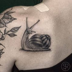 Snail tattoo on Lauras left shoulder blade. Tattoo...
