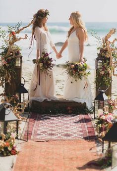 Picture of driftwood, candle lanterns, bright and pastel blooms and boho rugs to decorate the boho beach wedding ceremony space Lesbian Beach Wedding, Lesbian Wedding Photos, Bohemian Beach Wedding, Lgbt Wedding, Wedding Ceremony, Beach Ceremony, Lesbian Couples, Muslim Couples, Hair Wedding