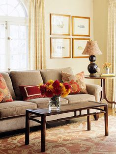 couch with throw pillows and tables on a red and beige rug