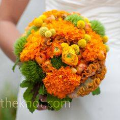 Orange Bridal Bouquet    Bunches of ranunculus, cockscomb, craspedia and greenery were gathered into a tight, circular shape to match the theme.