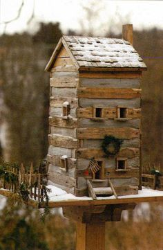 Log living for our feathered friends - handmade two story cabin with a frost of snow - even a nice sitting porch. Entrance is tiny - perhaps for a pair of wrens or hermit warblers high up in a coniferous tree