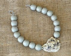 Limited Edition Style The Moon River Long  Handmade oyster shell necklace with white beads similar to mother of pearl. Measures approximately 23.5 in length. Toggle closure. Makes the perfect statement piece for every outfit from classy to casual! NOTE: Every necklace is one of a kind - the necklaces pictured are representative of the one you will receive. Each oyster shell is hand selected.  See our other listings for many more styles.  See more at dixiedelightsonline.com
