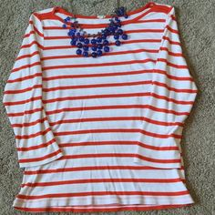 Orange Stripe Boatneck Tee Cotton boat neck tee from J Crew featuring red-orange stripes and 3/4 length sleeves. There is some pilling from normal wear and washing, but the shirt is still very wearable! J. Crew Tops