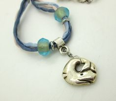 A happy little whale made of Mykonos silver, dances along on shaded silk cords of blue, and is accented with Czech glass beads. Necklace measures 25 inches in total length, and is closed iwth a pewter decorative S-clasp.  For more unique jewelry, please visit Elementals on Etsy at: https://www.etsy.com/shop/Elementalsjw?ref=hdr_shop_menu