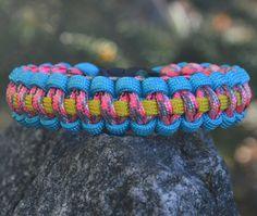 Slim Paracord Bracelet Outside Color= Turquoise    Inside Color= Pink Camo    Center Line= Yellow