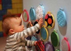 DIY Sensory Wall for baby. Tuck different fabric scraps in embroidery hoops and attach to wall where they can reach :)