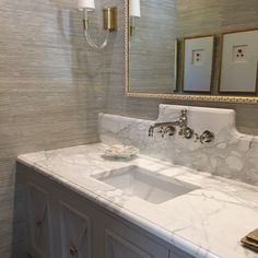 Chic gray powder room features walls clad in gray grasscloth lined with a gray washstand fitted ...