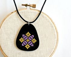 Modern Cross Stitch Necklace, Black Acrylic with Purple and Yellow Folk Art Design. $45.00, via Etsy.