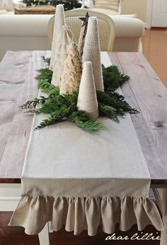Made the table runner from leftover tree skirt drop cloth (pleated instead of ruffled). Foliage from green space. Made cone trees with cardstock and used burlap, drop cloth, twine, and lace to make variations of trees. Total cost about $10.