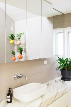 Jenna Spence's 'Mister Moss' suspended plant balls hang from the bathroom ceiling.  Photo - Brooke Holm, production – Lucy Feagins / The Design Files.