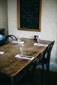 rustic table w/ black chairs & chalkboard