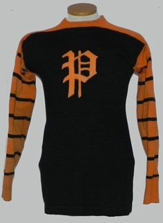 Beautiful Circa 1920's Spalding Brand Orange and Black Football Jersey.  This jersey features an attractive gothic style P on its chest with black and orange striping down each sleeve.  The jersey has a Spalding tag in its tail, that dates the jersey from the 1914 to Late 1920's time period.  The number 28 decorates the back of the jersey and there are reinforced areas on each elbow.