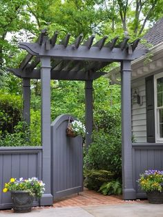 A mini-pergola and arched gate make for a grand entrance to this home's backyard.
