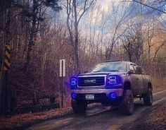 Lifted GMC Sierra truck - bright blue Led headlamps muddy