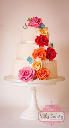 Three-tiered wedding cake with colorful cascading flowers #wedding #weddingcake #cake #flowers #spring