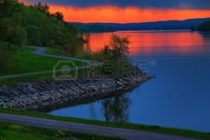 The rain is just starting to fall in the distance on the Ottawa River.  As the sun goes down it lights up the sky under the clouds. Stock Ph...