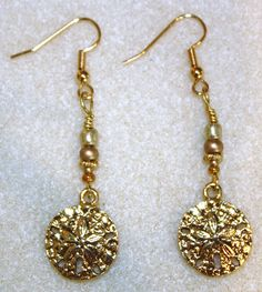 """Handcrafted by Teal Palmetto, LLC. These lovely golden sand dollars are eager to be added to your jewelry collection! These """"focals"""" are not beads, but rather metal charms. They *do* make a lovely pair of earrings, especially with their """"antiqued"""" finish. The sand dollars are accented with gold metal and gold seed beads. This pair of earrings has gold fish hook ear wires. Price: $16."""