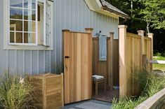 Outdoor shower with wood details to blend with architecture of house - looks like a fence