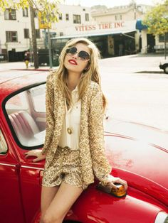 Gold shorts suit, white button down, pendant necklace and red lip