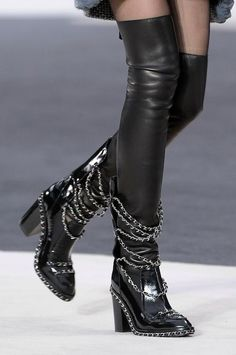 From the Fall 2013 Collection. Black patent leather Chanel round-toe boots with cutouts at front, chain accents throughout, silver-tone logo at counters, elasticized gores at sides, block heels and bu
